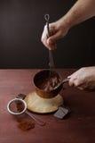 De mannelijke handen beweegt gesmolten chocoladewerveling in pan op de houten achtergrond Royalty-vrije Stock Foto's