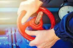 De mannelijke handen draaien de rode klep in het ketelruim royalty-vrije stock foto