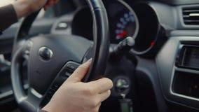 De mannelijke handen draaien stuurwiel van moderne auto, close-upmening stock video