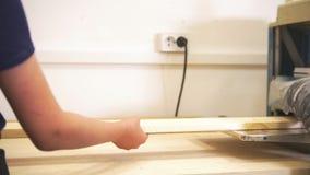 De mannelijke handen gaat een houten straal door de professionele timmerwerkmachine over stock footage