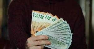 De mannelijke handen geven me Amerikaanse dollars en euro geld stock footage