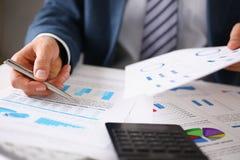 De mannelijke handen houden documenten met financiële statistieken stock afbeelding