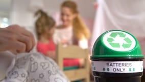 De mannelijke handen nemen de gebruikte batterijen van het stuk speelgoed en zetten hen in de speciale recyclingsdoos Kind en Mam stock video