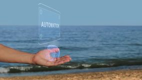 De mannelijke handen op het strand houden een conceptueel hologram met de tekstautomatisering