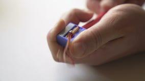 De mannelijke handen scherpen het rode potlood stock videobeelden