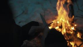 De mannelijke handen scherpt potlood over kampvuur met springmesmes stock videobeelden
