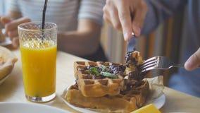 De mannelijke handen snijdt yummy Belgische wafels met een mes en een vork in restaurant stock foto