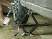 De mannelijke handen sponnen het wiel van de auto in de garage Stock Afbeelding