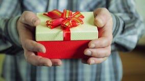 De mannelijke handen trekken een doos met een Kerstmis erachter verrassing van terug stock videobeelden