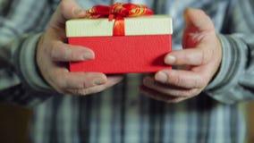 De mannelijke handen trekken terug van achter de doos met een Kerstmisgift Close-up stock footage