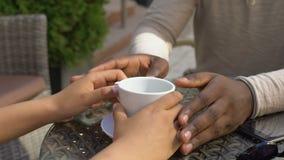De mannelijke handen van de holdingsvrouw, paar het drinken koffie in ochtendkoffie, nabijheid stock footage