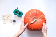 De mannelijke handen verfraaien een Halloween-pompoen op een witte achtergrond Stock Afbeeldingen