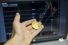 De mannelijke holding van de zakenmanhand bitcoin op een achtergrond van de groeigrafiek op het scherm van laptop Virtueel geldco royalty-vrije stock afbeelding