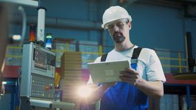 De mannelijke ingenieur met een tablet werkt naast het machtspaneel stock footage