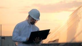 De mannelijke ingenieur neemt een zonnebouw waar en werkt met laptop stock footage