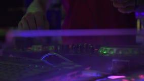 De mannelijke jockey van de handschijf op het dek van DJ voor het mengen van huismuziek op discopartij Speel de dansmuziek van me stock videobeelden