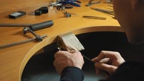 De mannelijke juwelier maakt wodden model van ring gebruikend instrumenten langzame motie stock video