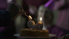 De mannelijke kaarsen van de handverlichting op cake 90 van de oude moederjaar verjaardag, familiezorg stock videobeelden