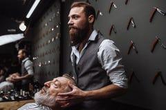 De mannelijke kapper kiest baardontwerp voor oud-verouderde cliënt bij kapper stock afbeelding