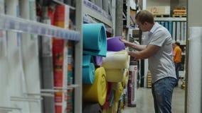 De mannelijke klant kiest schuimrubberisolatie in opslag van bouwmaterialen stock video