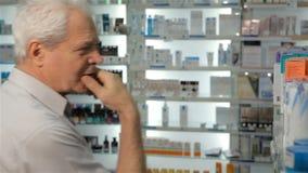 De mannelijke klant kiest wat geneeskunde bij de drogisterij stock videobeelden