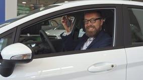 De mannelijke klant toont sleutel door het autoraam stock foto