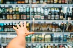 De mannelijke klantenhand bereikt voor alcoholische producten stock foto