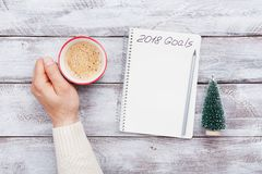 De mannelijke kop van de handgreep van koffie en notitieboekje met doelstellingen voor 2018 Planning en motivatie voor het nieuwe Royalty-vrije Stock Foto