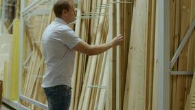 De mannelijke koper kiest houten raad in winkel van bouwmaterialen stock footage