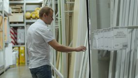 De mannelijke koper kiest laminaat in winkel van bouwmaterialen stock videobeelden