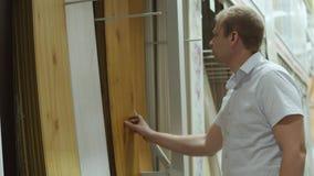 De mannelijke koper kiest laminaat in winkel van bouwmaterialen stock video