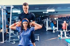 De mannelijke laag leidt jonge vrouw in sportkleding op die sommige gewichten opheffen stock afbeeldingen