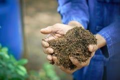 De mannelijke landbouwers gebruiken allebei clayed handen met rijstschil Royalty-vrije Stock Foto's