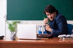 De mannelijke leraar die in het klaslokaal drinken stock foto