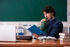De mannelijke leraar die in het klaslokaal drinken royalty-vrije stock afbeeldingen