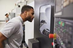 De mannelijke Machines van Ingenieurswatching progress of CNC in Fabriek royalty-vrije stock fotografie
