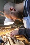 De mannelijke maker die van de vakmanviool aan een nieuwe viool werken stock afbeelding