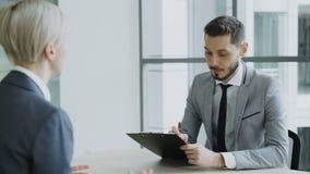 De mannelijke manager die van u baangesprek met jonge vrouw in kostuum hebben en op haar samenvattingstoepassing in modern bureau stock video
