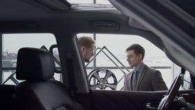 De mannelijke manager en custimer gaat vanaf luxeauto in autocenter, langzame motie stock videobeelden