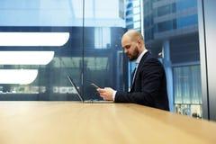De mannelijke manager let op video op celtelefoon tijdens het werk aangaande draagbaar netto-boek stock fotografie