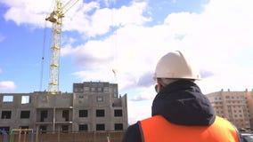 De mannelijke meester in een signaalvest en een helm houdt toezicht op de bouw van een woonpaneelhuis, exemplaarruimte stock video