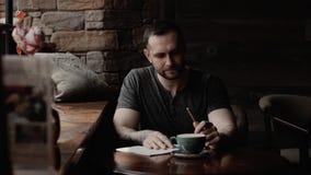 De mannelijke mensenzitting door het venster met getatoeeerde wapens in koffie neemt nota's in agenda stock videobeelden