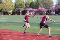De mannelijke Middelbare schoolatleten gaan de knuppel in het X400-4 relais in een spoor over samenkomen stock afbeelding