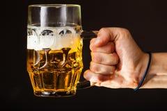 De mannelijke mok van de handholding bier Stock Afbeeldingen
