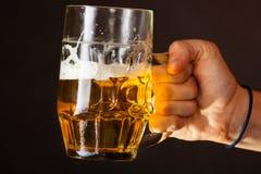 De mannelijke mok van de handholding bier Stock Foto's
