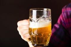 De mannelijke mok van de handholding bier Stock Foto