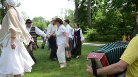 De mannelijke musicus geniet spel van harmonika en de mensen dansen in paren stock footage