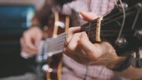 De mannelijke musicus speelt de gitaar, dicht omhoog overhandigt stock foto
