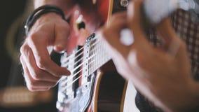 De mannelijke musicus speelt de gitaar, dicht omhoog overhandigt, nadruk op de gitaar fretboard stock foto