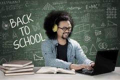De mannelijke muziek van de studentenhoorzitting op een hoofdtelefoon Stock Afbeeldingen